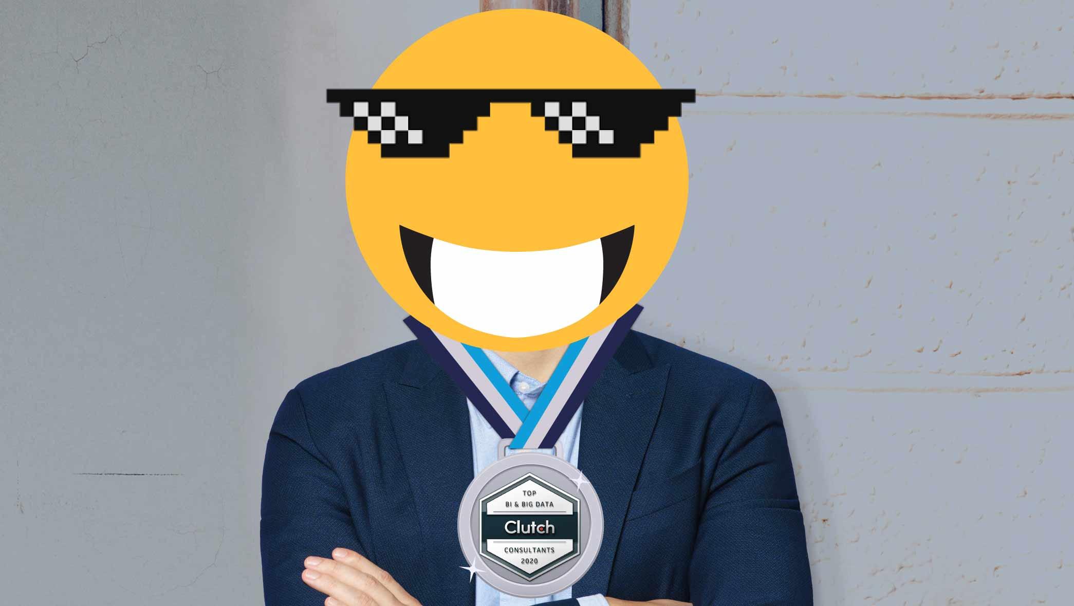 Meme: emoji com óculos de sol pretos, sorrindo, com corpo humano de camisa social azul e gravata clara, usando medalha pendurada no pescoço de empresa líder em data science e analytics na América Latina.